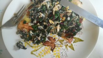 Scrambled eggs with silverbeet and garlic on toast